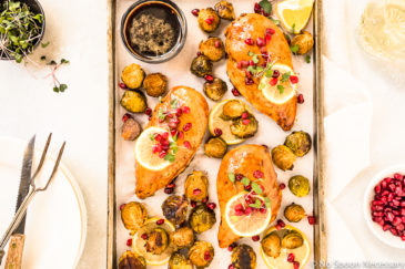 Overhead shot of a Sheet Pan containing Honey Balsamic Chicken & Brussels Sprouts garnished with lemon slices, pomegranate arils and micro greens; with a stack of plates, knife, meat fork, glass of wine, and small bowls of pomegranate arils and micro greens surrounding the pan.