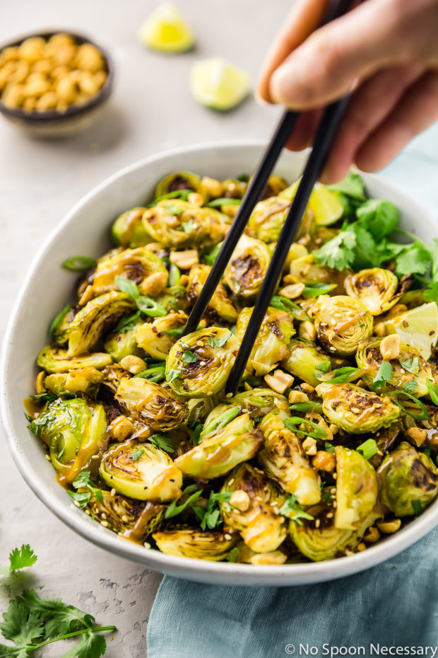 45 degree angle shot of a neutral colored bowl filled with Roasted Asian Brussels Sprouts drizzled with peanut sauce and a hand holding black chop stick picking up a sprout, with a pale blue linen, ramekin of peanuts and lime wedges blurred in the background.
