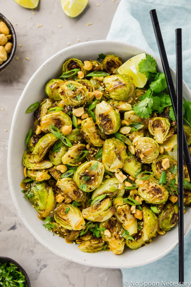 Overhead, close-up shot of a neutral colored bowl filled with Roasted Asian Brussels Sprouts drizzled with peanut sauce with black chopsticks resting on the side of the bowl and a pale blue linen, ramekin of peanuts, ramekin of sliced scallions and lime wedges surrou