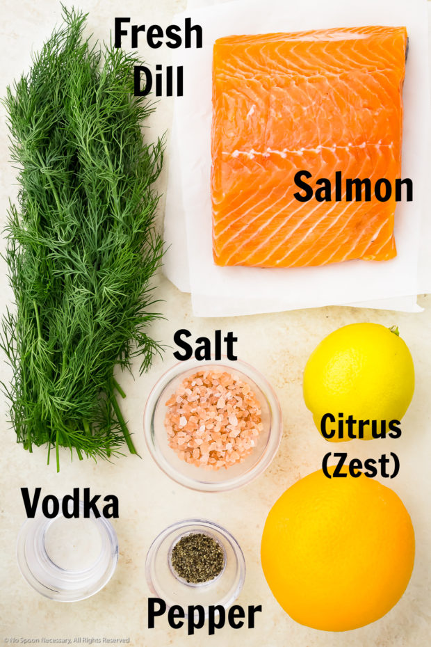 Overhead photo of all the ingredients needed to make gravlax neatly organized on a wood surface.