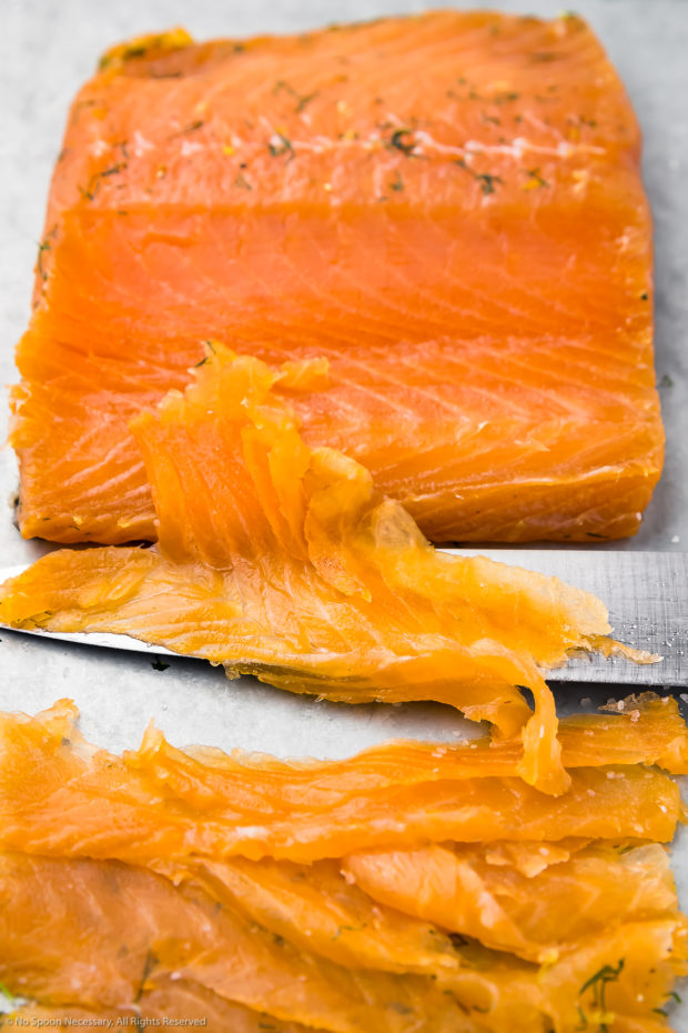 45 degree angle photo of a center cut filet of gravlax that has been partially carved and sliced on the bias, with the slicing knife laying in front of the salmon. (Photo showing how to slice cured salmon at home.)