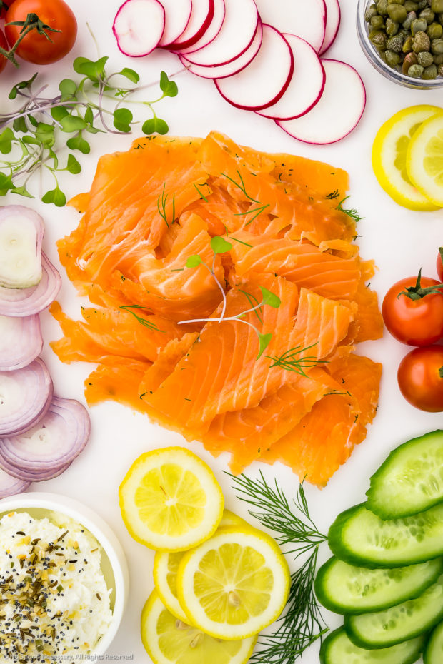 Overhead photo of a white cheese board neatly organized with an array of cured salmon gravlax, sliced shallots, vine ripe tomatoes, sliced radishes, sliced lemons, sliced cucumbers, a small bowl of capers, fresh herbs and a bowl of everything spice cream cheese.