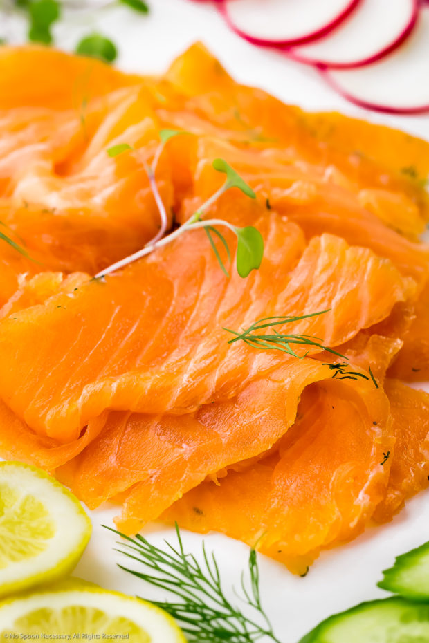 45 degree angle, close-up photo of an pile of sliced homemade gravlax salmon.