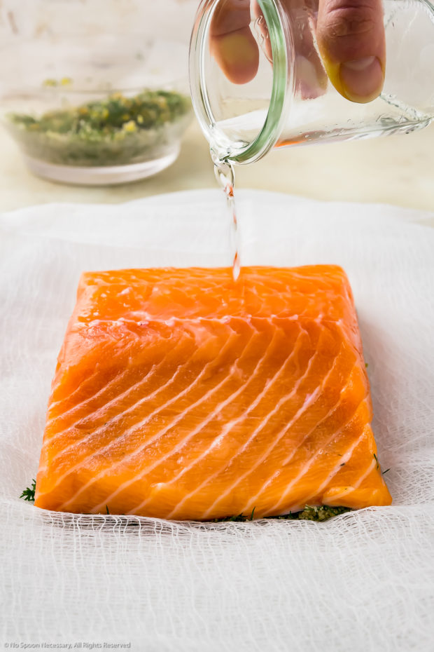 Straight on shot of a hand holding a small glass jar of vodka and pouring it on top of a filet of salmon - step 4 of the recipe