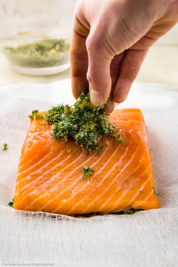 Straight on photo of a hand putting a dry cure of citrus zest and dill on top of a filet of salmon - step 4 of the recipe.