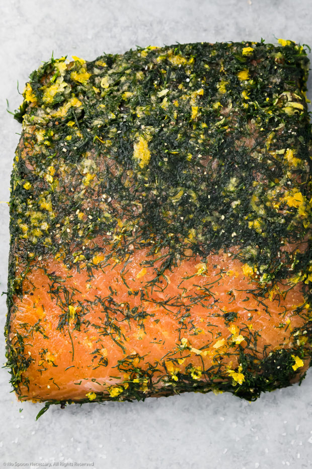 Overhead photo of a filet of salmon that has been salt-cured and wrapped with fresh dill, with part of the dry brine scrapped off the top exposing the cured salmon.