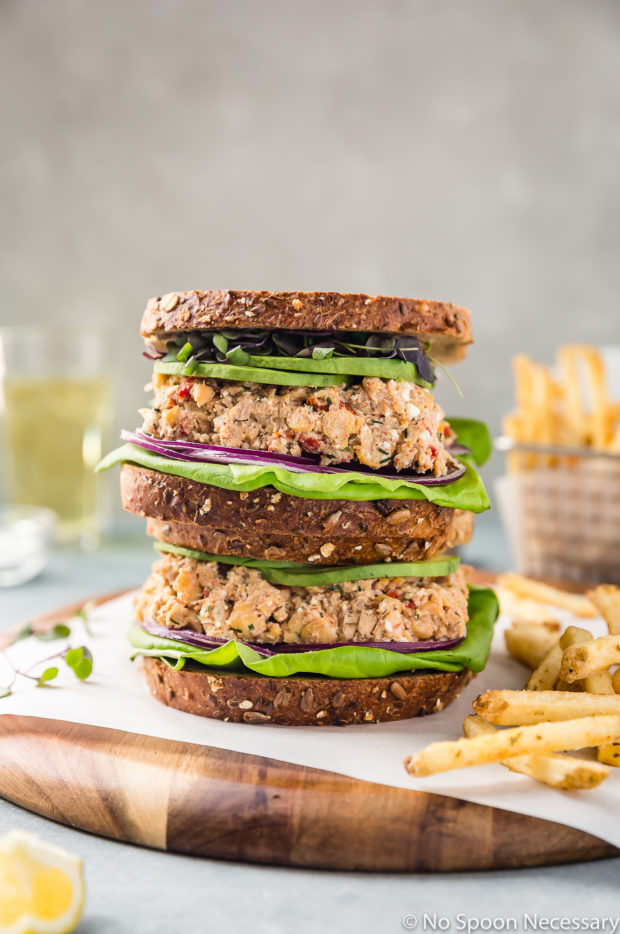 Straight on shot of two Mediterranean Smashed Chickpea Salad Sandwiches with micro greens, sliced avocado, red onions and lettuce on whole grain bread stacked on top of each other on a wood platter with a basket of french fries and glass of beer blurred in the background.