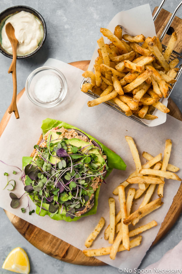 Overhead shot of an open faced Mediterranean Smashed Chickpea Salad Sandwich with micro greens, sliced avocado, red onions and lettuce a wood platter lined with parchment paper with a basket of french fries, ramekin of tahini mayonnaise, pinch bowl of salt and lemon wedge surrounding the sandwich.