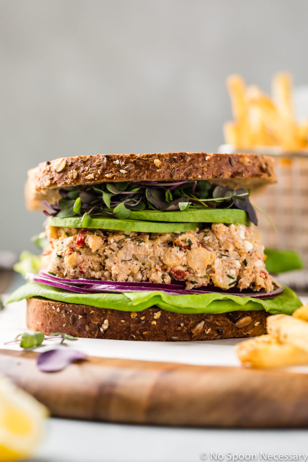 Straight on shot of a Mediterranean Smashed Chickpea Salad Sandwich with micro greens, sliced avocado, red onions and lettuce with whole grain bread on a wood platter with a basket of french fries blurred in the background.