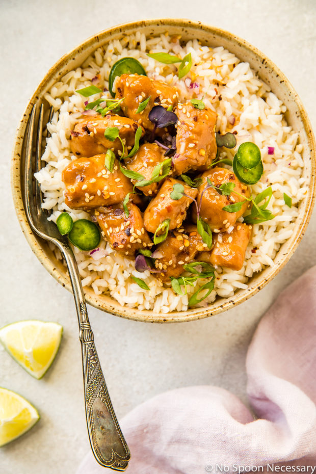 Overhead shot of a neutral colored bowl filled with rice and topped with Slow Cooker Bourbon Plum Chicken, with a fork inserted into the rice and a pale purple linen and lime wedges tucked in the bottom corners of the shot.