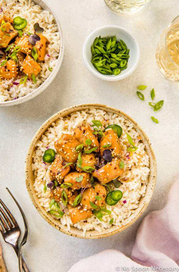 Overhead shot of a neutral colored bowl filled with rice and topped with Slow Cooker Bourbon Plum Chicken, with a pale purple linen, forks, additional bowl of chicken, small bowl of sliced scallions, and wine glasses surrounding the main bowl.