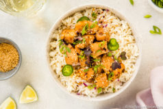 Overhead, landscape shot of a white bowl filled with rice and topped with Slow Cooker Bourbon Plum Chicken, with a pale purple linen, lime wedges, small bowl of sesame seeds, wine glass and sliced scallions surrounding the bowl.