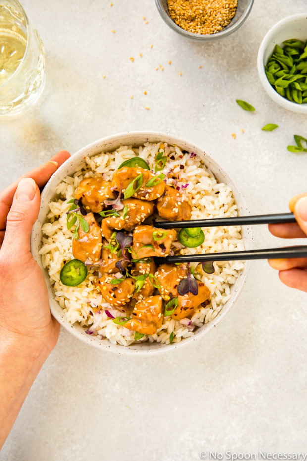 Overhead shot of a neutral colored bowl filled with rice and topped with Slow Cooker Bourbon Plum Chicken, with a hand holding the bowl and another hand holding chopsticks picking up a piece of chicken, with a glass of wine and small bowls of sesame seeds and sliced scallions tucked into the upper corners of the shot.