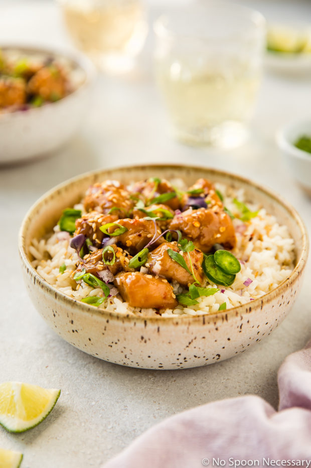 45 degree angle shot of a neutral colored bowl filled with rice and topped with Slow Cooker Bourbon Plum Chicken, with a pale purple linen, lime wedges, additional bowl of chicken, small bowl of sliced scallions, and wine glasses blurred around the main bowl.