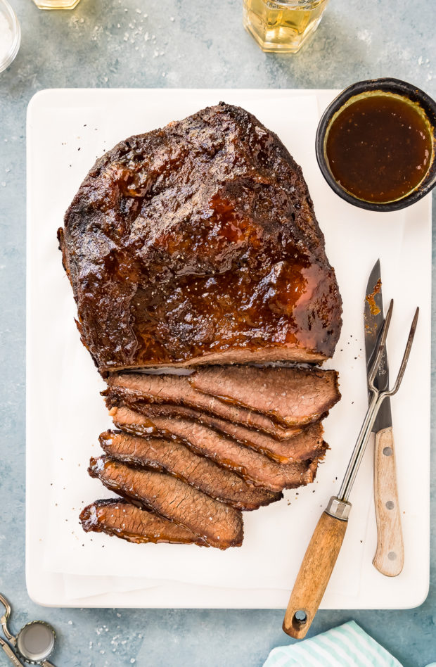 Overhead photo of Slow Cooker Beef Brisket partially sliced on a white cutting board with a ramekin of sauce, meat fork and knife to the side and two glasses of beer, bottle caps, bottle opener and ramekin of salt surrounding the board.