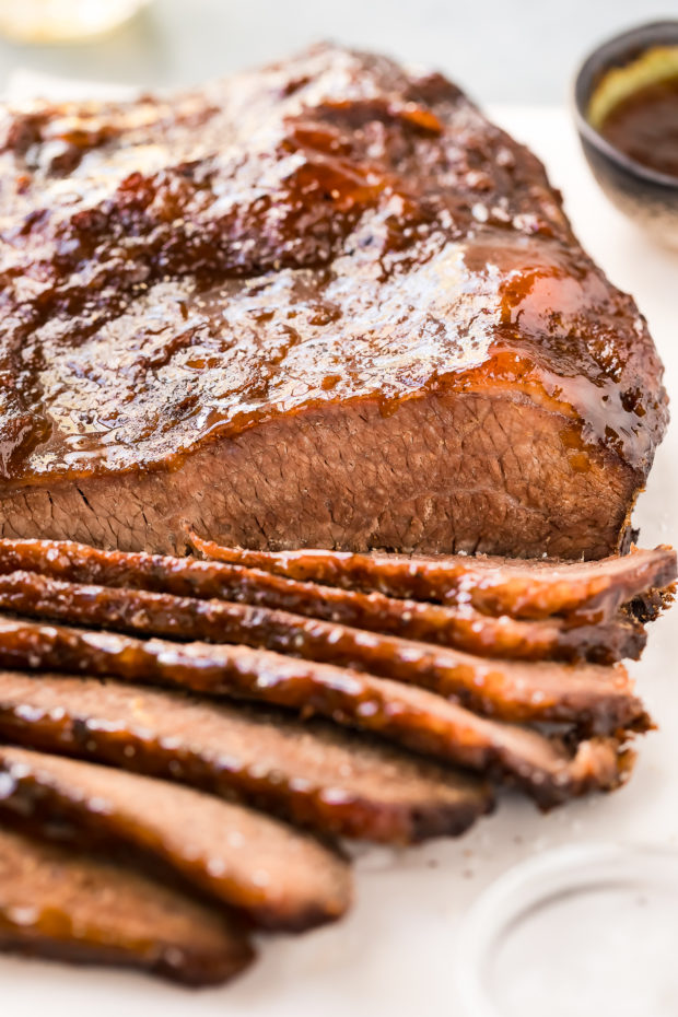 Straight on photo of easy Beef Brisket partially sliced on a white cutting board with a small bowl of salt blurred in the front corner and a small bowl of sauce blurred in the background.