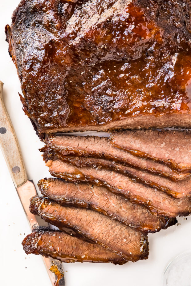 Overhead close-up photo of Slow Cooker Brisket brushed with an apricot glaze partially sliced on a white cutting board with a wood handled knife tucked under a few slices of the brisket.
