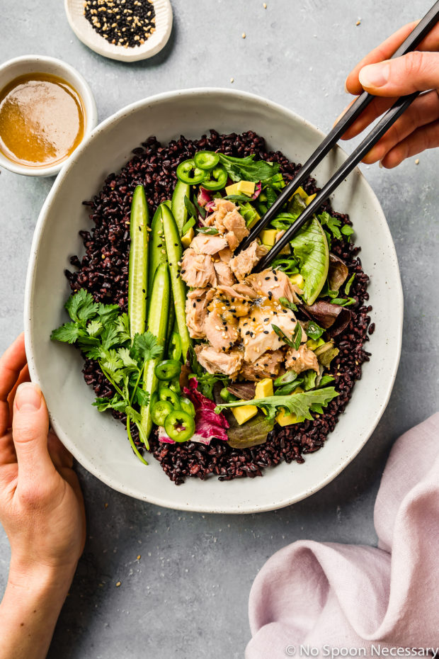 Overhead shot of Asian Avocado Tuna Salad Grain Bowl in a neutral colored serving bowl a persons hand holding the bowl and another hand holding black chopsticks; with a purple linen, ramekin of honey miso dressing and ramekin of sesame seeds surrounding the serving bowl.