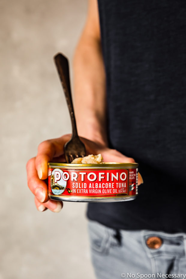 Straight on shot of a person holding a can of Bella Portofino Tuna - one of the main ingredients in an Asian Avocado Tuna Salad Grain Bowl.
