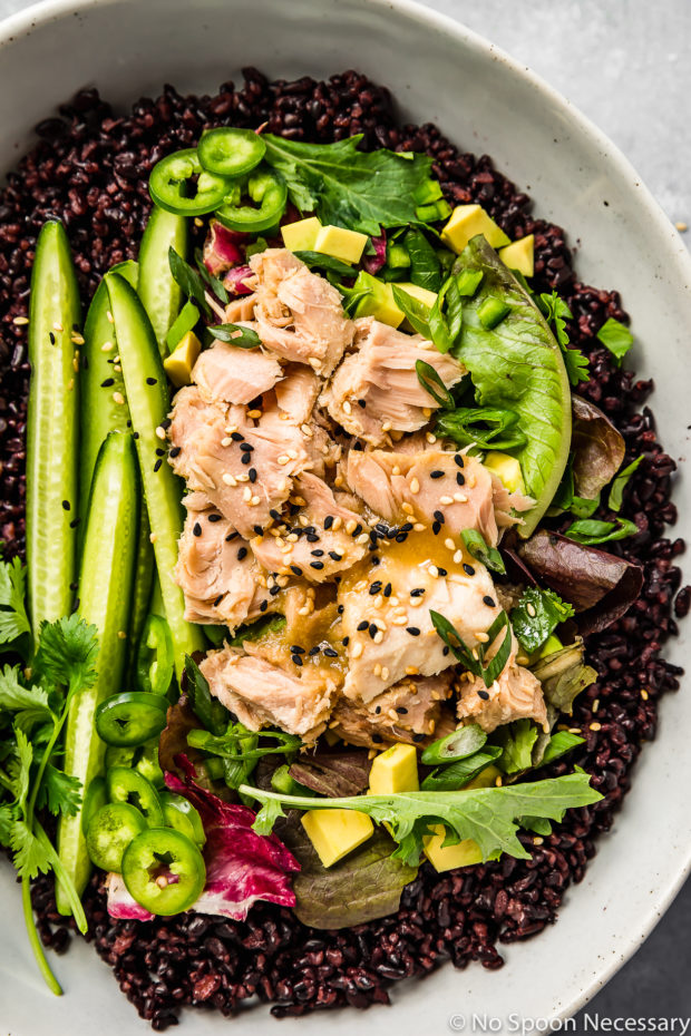 Overhead, up close shot of Asian Avocado Tuna Salad Grain Bowl in a neutral colored serving bowl.