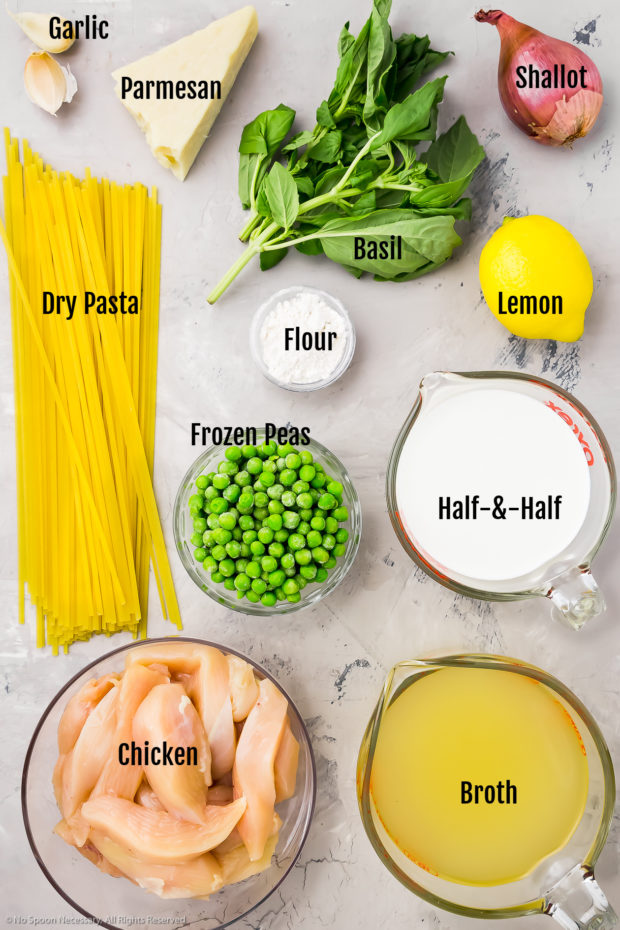 Overhead photo of all the ingredients needed to make Creamy Lemon Chicken Pasta recipe neatly organized by individual ingredient on a gray surface.