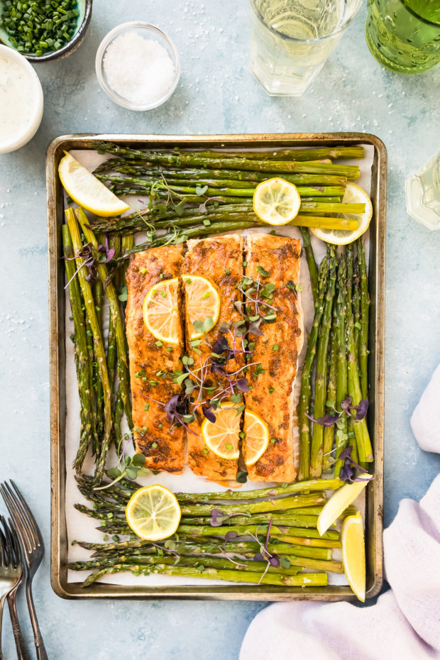 Overhead shot of baked Lemon Dijon Salmon and Asparagus on a sheet pan with a pale purple linen, forks, wine glasses, ramekin of chopped chives and small bowl of Basil Aioli surrounding the pan.