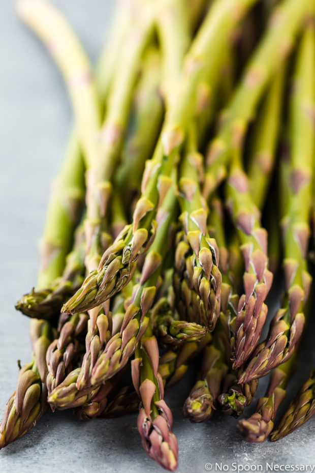 Angled up close shot of a bunch of asparagus - one of the main ingredients in the recipe for Sheet Pan Lemon Dijon Salmon & Asparagus.