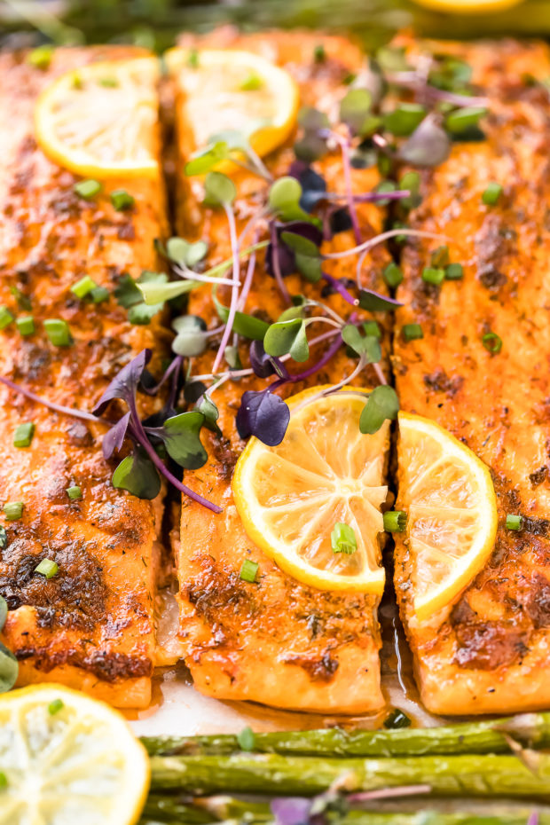 Angled, up close shot of Sheet Pan Lemon Dijon Salmon and Asparagus garnished with lemon slices and micro greens.
