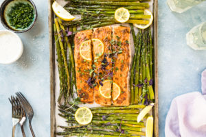 Overhead, landscape shot of baked Lemon Dijon Salmon and Asparagus on a sheet pan with a pale purple linen, forks, wine glasses, ramekin of chopped chives and small bowl of Basil Aioli surrounding the pan.