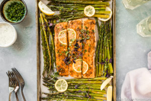 Overhead, landscape shot of Sheet Pan Lemon Dijon Salmon and Asparagus with a pale purple linen, forks, wine glasses, ramekin of chopped chives and small bowl of Basil Aioli surrounding the pan.