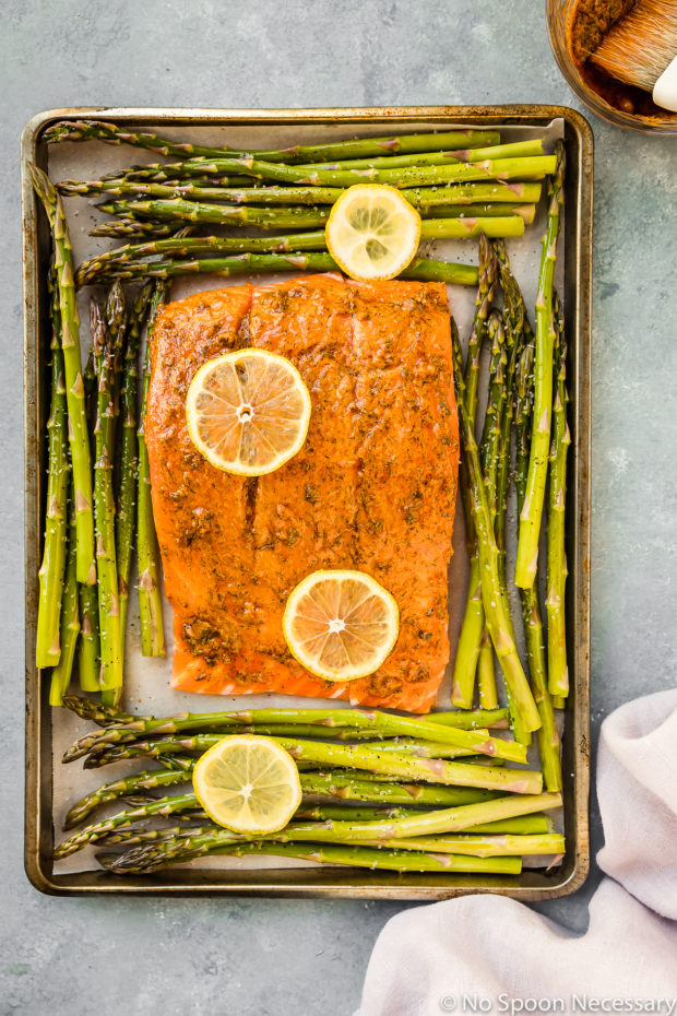 Overhead shot of Sheet Pan Lemon Dijon Salmon and Asparagus before roasting (step 5 in the recipe) with a pale purple linen and bowl of lemon dijon sauce surrounding the pan.