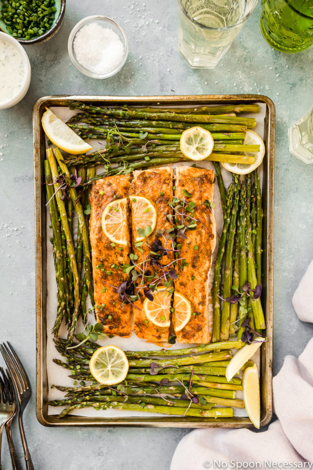 Overhead shot of Sheet Pan Lemon Dijon Salmon and Asparagus with a pale purple linen, forks, wine glasses, ramekin of chopped chives and small bowl of Basil Aioli surrounding the pan.