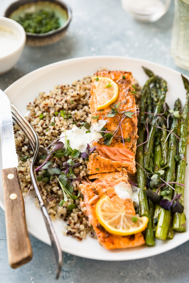 Angled shot of plated Sheet Pan Lemon Dijon Salmon and Asparagus with quinoa and basil aioli; with a knife and fork on the plate and a wine glass, ramekin of chopped chives and small bowl of Basil Aioli surrounding the plate.