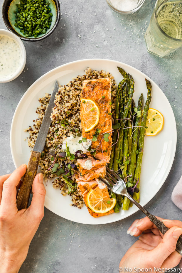 Overhead shot of plated Sheet Pan Lemon Dijon Salmon and Asparagus with quinoa and basil aioli; two hands holding a knife and fork and a wine glass, ramekin of chopped chives and small bowl of Basil Aioli surrounding the plate.