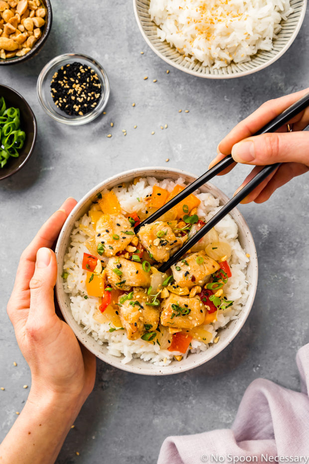 Overhead shot of a white bowl filled with rice and Sheet Pan Thai Peanut Chicken, onions and peppers with one hand holding the bowl and another hand holding a pair of chopsticks and a purple linen, bowl of rice, and ramekins of peanuts, sesame seeds and scallions surrounding the main bowl.
