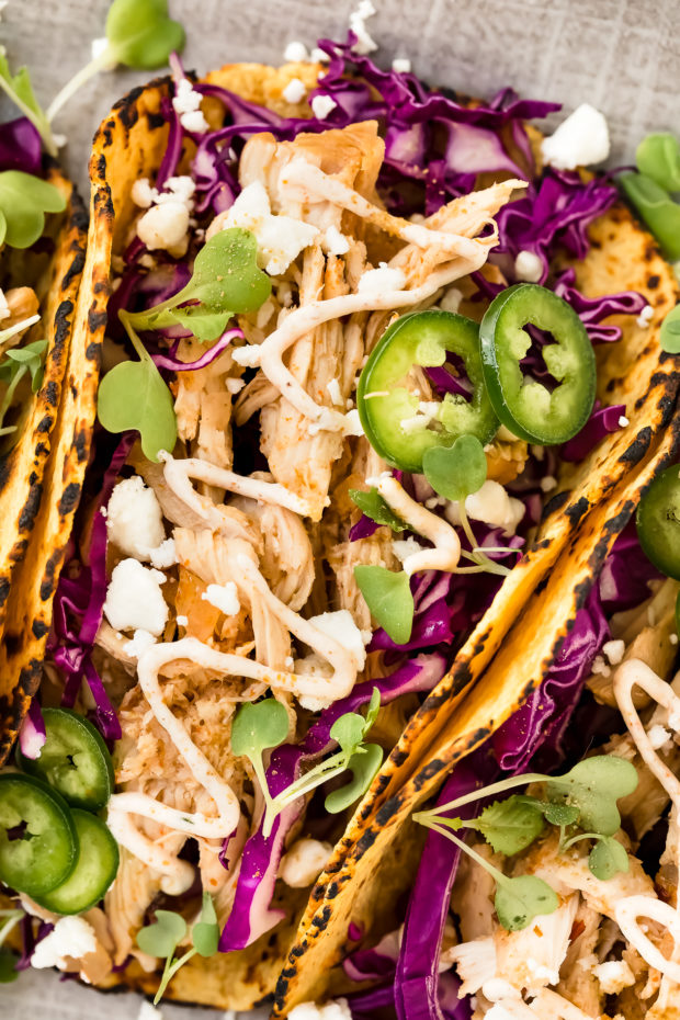 Overhead, up close shot of a a Baja Beer Chicken Tacos on a gray platter garnished with jalapeno slices, micro greens and cotija cheese.
