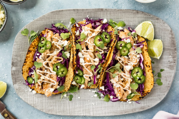 Overhead, landscape photo of a gray platter of Beer Chicken Tacos on a blue surface with a pale purple linen, lime wedges, small knife, and bowls of salt, cotija cheese and baja sauce surrounding the platter.