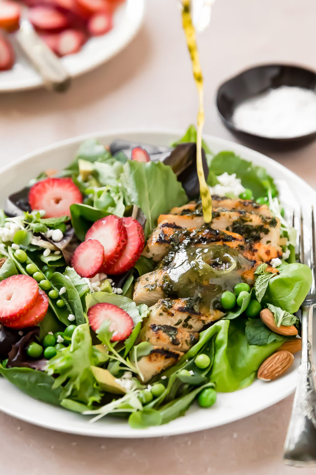 Angled, up-close shot of a herb vinaigrette being drizzled on a Strawberry Salad with Grilled Chicken on white plate with a fork; with a plate of sliced strawberries and small ramekin of salt blurred in the background.