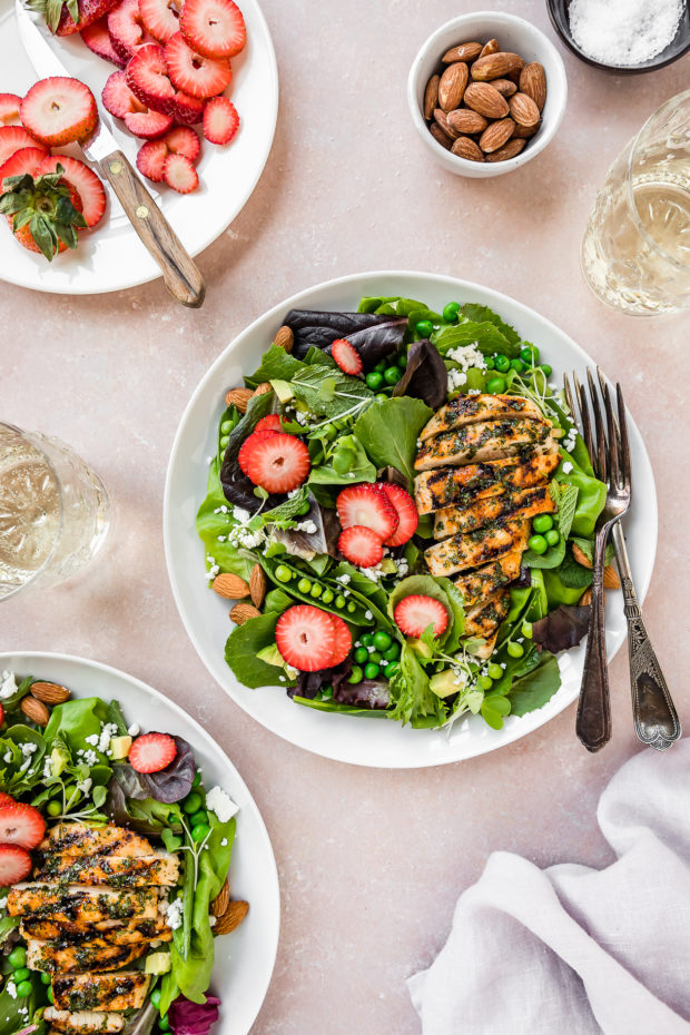 Overhead shot of two Spring Pea & Strawberry Salads with Grilled Chicken on white plates with a plate of sliced strawberries, wine glasses, pale purple linen, bowl of almonds, and small ramekin of salt surrounding the plates.