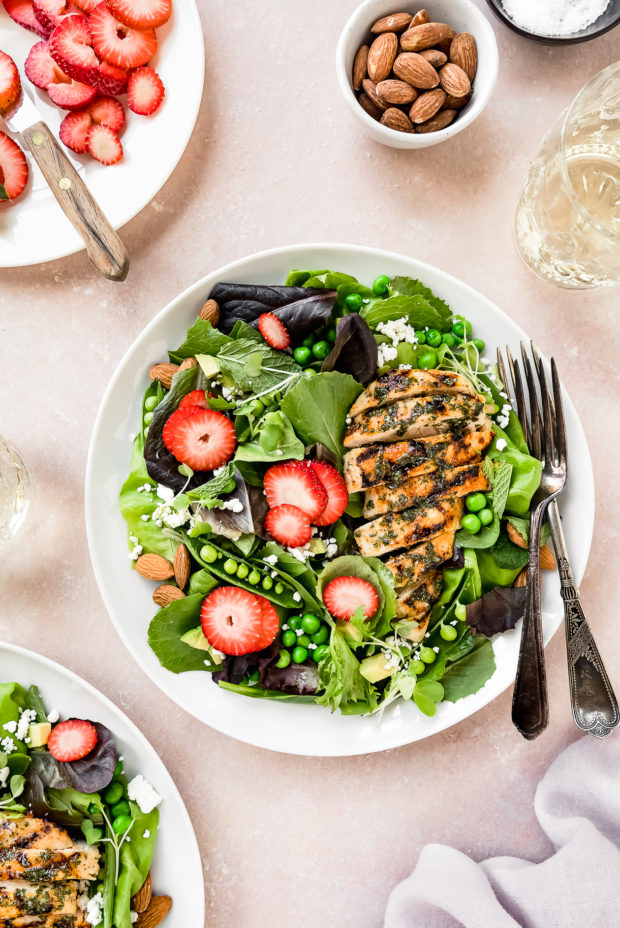 Overhead shot of two Strawberry Salads with spinach and grilled chicken on white plates with a plate of sliced strawberries, wine glasses, pale purple linen, bowl of almonds, and small ramekin of salt surrounding the plates.