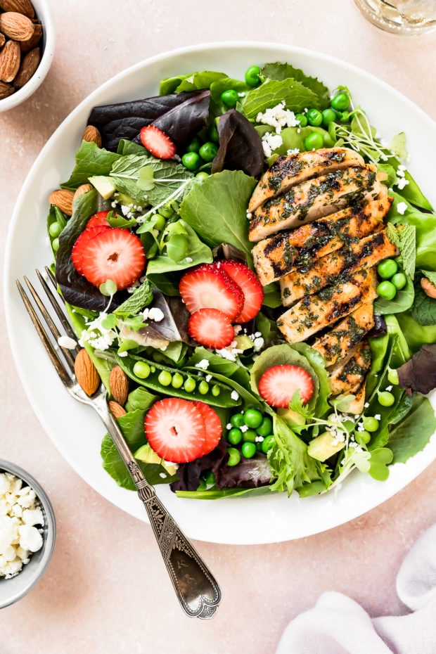 Overhead photo of a Fresh Strawberry Spinach Salad topped with grilled chicken on a white plate with a fork inserted into the salad and ramekins of crumbled goat cheese and almonds next to the plate.