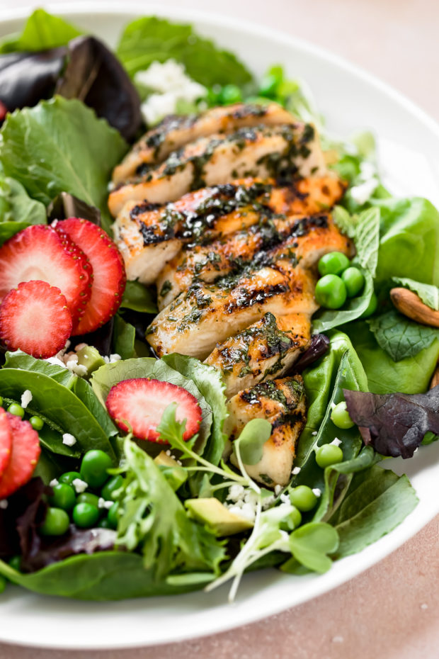 Angled shot of a Strawberry Salad with spinach, grilled chicken, fresh peas and avocado on white salad plate.