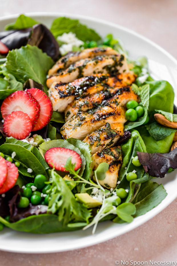 Angled shot of a Spring Pea & Strawberry Salad with Grilled Chicken on white plate.