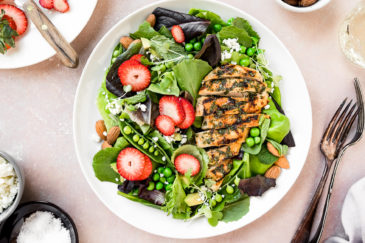 Overhead, landscape shot of a Strawberry Spinach Salad with Grilled Chicken on a white plate with a plate of sliced strawberries, wine glasses, pale purple linen, bowl of almonds, and small ramekin of salt, bowl of feta and forks surrounding the plates.
