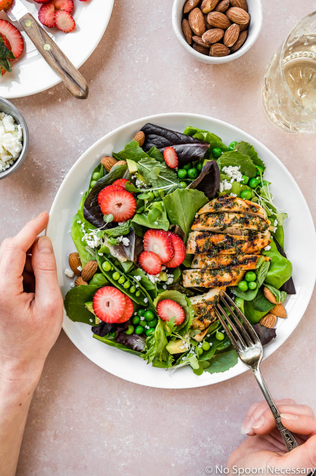 Overhead shot of Spring Pea & Strawberry Salad with Grilled Chicken on white plate with one hand holding the plate and another hand holding a fork inserted into the chicken; with a plate of sliced strawberries, bowl of almonds, bowl of feta and wine glass surrounding the plate.