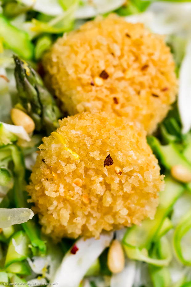 Angled, up close shot of panko crusted baked goat cheese on top of an Asparagus Salad.