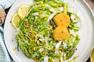 Overhead, landscape shot of Shaved Raw Asparagus Salad on a light gray plate with a pale teal stripped linen and small glass bowl of vinaigrette surrounding the plate.