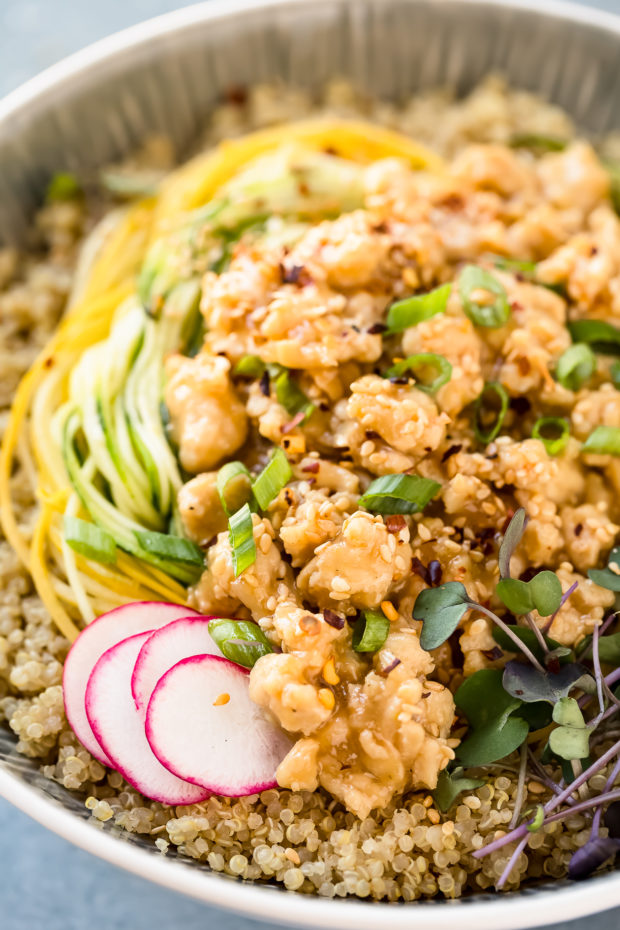 Angled, up close shot of a Healthy Honey Lemon Chicken served over quinoa and squash noodles and garnished with sliced radishes.