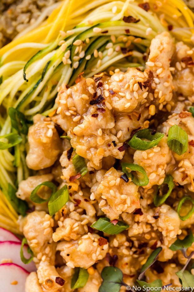 Overhead, up close shot of a Healthy Honey Lemon Chicken Quinoa Bowl garnished with sliced scallions and sesame seeds.