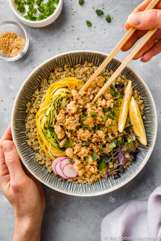Overhead shot of a Healthy Honey Lemon Chicken Quinoa Bowl garnished with lemon wedges on a blue surface with a hand holding chopsticks eating out of the bowl and another hand holding the bowl; there is a pale purple linen and ramekins of scallions and sesame seeds surrounding the bowl.